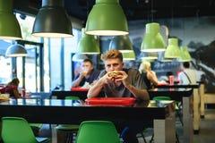 坐在一家快餐餐馆和吃一个开胃汉堡的年轻美丽的学生 免版税库存图片