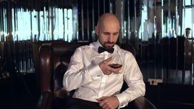 坐在一家餐馆的典雅的人用科涅克白兰地 股票录像