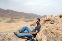 坐在一座山顶部的远足者人在沙漠 免版税库存图片