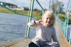 坐在一座老木下垂桥梁的一个愉快的白肤金发的男孩 图库摄影