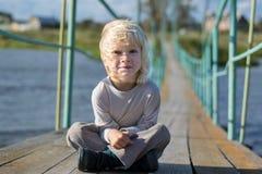 坐在一座老木下垂桥梁的一个愉快的白肤金发的男孩 免版税图库摄影
