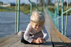 坐在一座老木下垂桥梁的一个愉快的白肤金发的男孩 免版税库存图片