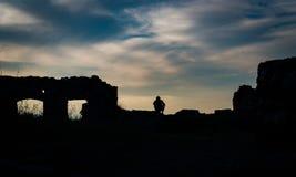 坐在一座被破坏的城堡边缘的人剪影 免版税图库摄影
