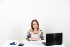 坐在一张书桌后的女孩在办公室 一在白的背景 免版税库存照片
