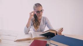 坐在一张书桌在办公室学习书的妇女为检查做准备 股票录像