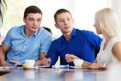 坐在一张书桌的年轻商人在办公室, negoti的 免版税库存照片