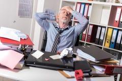 坐在一张杂乱书桌的劳累过度的商人 库存图片