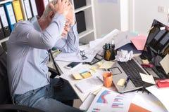 坐在一张杂乱书桌的劳累过度的商人 免版税图库摄影