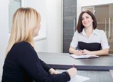 坐在一张桌上的两名妇女在办公室 白肤金发和深色在工作面试或者会议 免版税库存照片