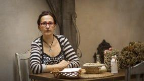 坐在一张桌上的妇女在一家老餐馆 库存图片