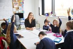 坐在一张桌上的小学孩子在有他们的女老师的一间教室,举他们的手 库存图片
