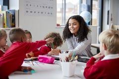 坐在一张桌上的微笑的女性婴儿学校老师正面图在有一个小组的教室学童 免版税图库摄影