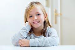 坐在一张桌上的美丽的白肤金发的孩子在厨房里 图库摄影
