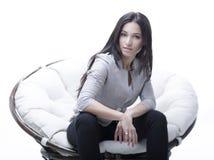 坐在一把圆的舒适软的大椅子的少妇 免版税图库摄影