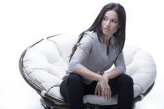 坐在一把圆的舒适软的大椅子的少妇 免版税库存图片