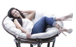 坐在一把圆的舒适软的椅子的现代少妇 图库摄影