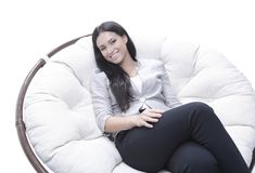 坐在一把圆的舒适软的椅子的现代少妇 免版税库存图片