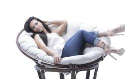 坐在一把圆的舒适软的椅子的现代少妇 免版税库存照片