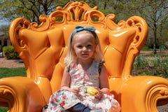 坐在一把明亮的橙色椅子的小女孩在庭院里 库存图片