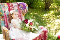 坐在一把明亮的葡萄酒扶手椅子的逗人喜爱的女孩 图库摄影