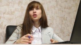 坐在一把椅子在办公室和谈和做在bloknot的美女笔记 年轻女性企业家工作 股票录像