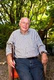 坐在一把椅子的年长人在他的庭院和神色非常frie里 库存照片