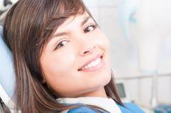 坐在一把牙齿椅子的微笑的女性患者特写镜头  免版税库存照片
