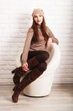 坐在一把白色圆的椅子的女孩 免版税库存图片