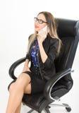 坐在一把皮革扶手椅子的西装的美丽的女孩 免版税库存图片