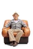 坐在一把皮革扶手椅子的年长人 免版税库存照片