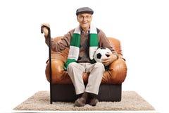 坐在一把皮革扶手椅子的年长足球迷 免版税图库摄影