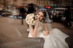 坐在一把皮革黑椅子的微笑的新娘在窗口附近 图库摄影