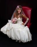 坐在一把红色椅子的白肤金发的新娘在工作室 库存图片