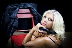 坐在一把红色椅子附近的白肤金发的探戈节目播音员画象  免版税图库摄影