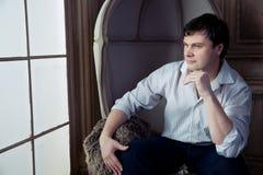 坐在一把老椅子的英俊的人 免版税图库摄影