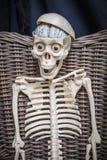 坐在一把藤椅的骨骼 图库摄影
