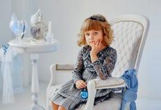 坐在一把豪华椅子的小女孩在一间明亮的屋子 免版税库存照片