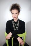 坐在一把绿色椅子的一个惊人的时兴的模型的画象,演播室射击 关闭新美丽的妇女纵向 库存照片