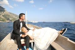 坐在一条木小船的新娘夫妇 免版税库存照片