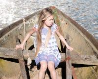 坐在一条老小船的美丽的白肤金发的女孩 免版税库存照片