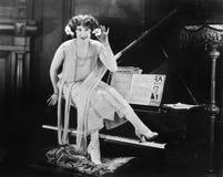 坐在一架大平台钢琴顶部的妇女(所有人被描述不更长生存,并且庄园不存在 供应商保单那 免版税库存照片