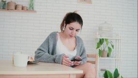 坐在一栋舒适公寓和浏览互联网的美丽的妇女 深色的女孩使用智能手机并且喝咖啡 免版税库存图片