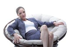 坐在一根圆的椅子藤条的女商人 免版税库存照片