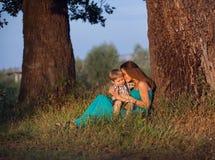 坐在一棵大树下的母亲和儿子 免版税图库摄影