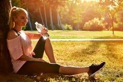 坐在一棵树的少妇在公园和饮用水 库存照片