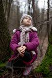 坐在一棵树附近的小女孩在秋天森林里 免版税库存照片