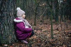坐在一棵树附近的小女孩在秋天森林里 免版税库存图片