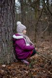 坐在一棵树附近的小女孩在秋天森林里 库存照片