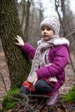 坐在一棵树附近的小女孩在秋天森林里 图库摄影