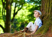 坐在一棵老树下的男孩,在森林里 库存照片